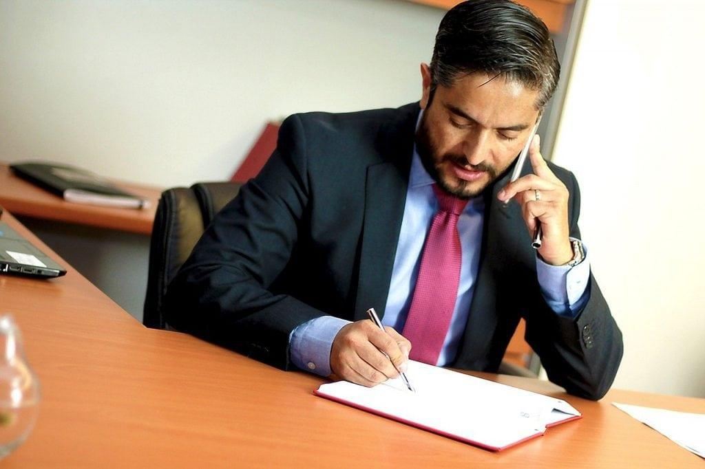 Mężczyzna w garniturze siedzący przy biurku i rozmawiający przez telefon