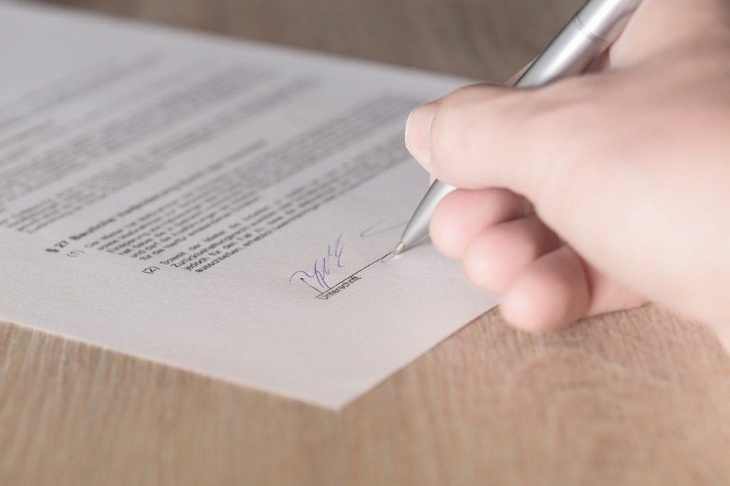 Ręka trzymająca długopis, którym podpisuje dokument
