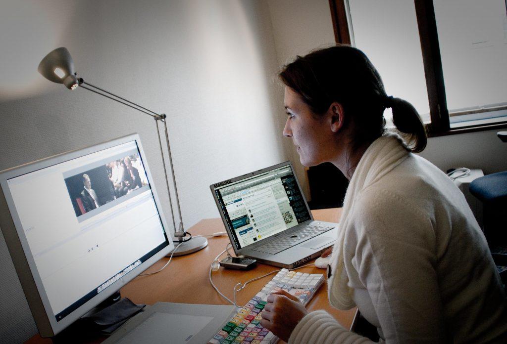 Kobieta siedząca przy monitorze i obok laptopa